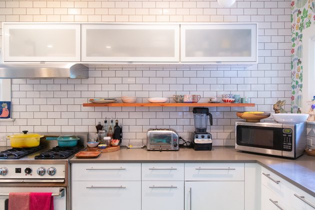 kitchen with subway tile, open shelving, white cabinetry, floral wallpaper