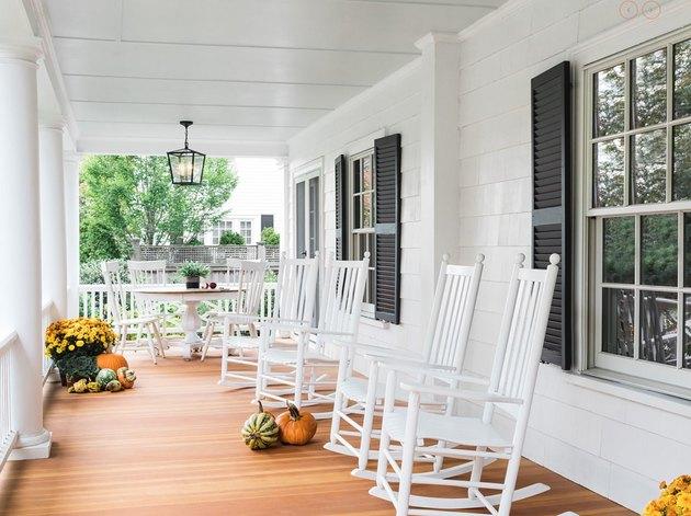 farmhouse porch idea with white rockers and fall decor
