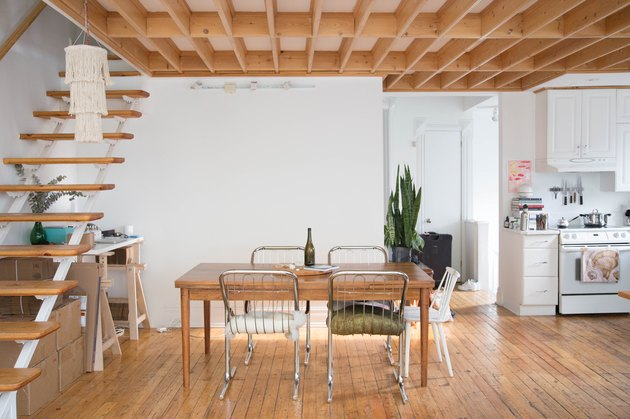 dining room with wood floors, open staircase, wood table, kitchen