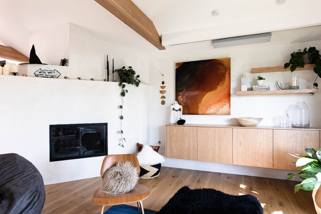 living room with fireplace, curved adobe wall, hardwood floors