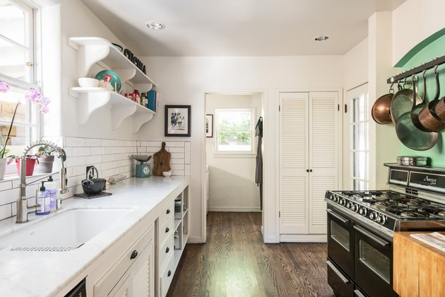 galley kitchen with double oven, white countertops, exposed shelving