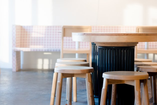 close up on table with wooden chairs, pink bench in background, concrete floors