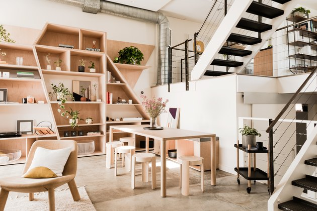 open living space with exposed stairs, chair, plywood shelving