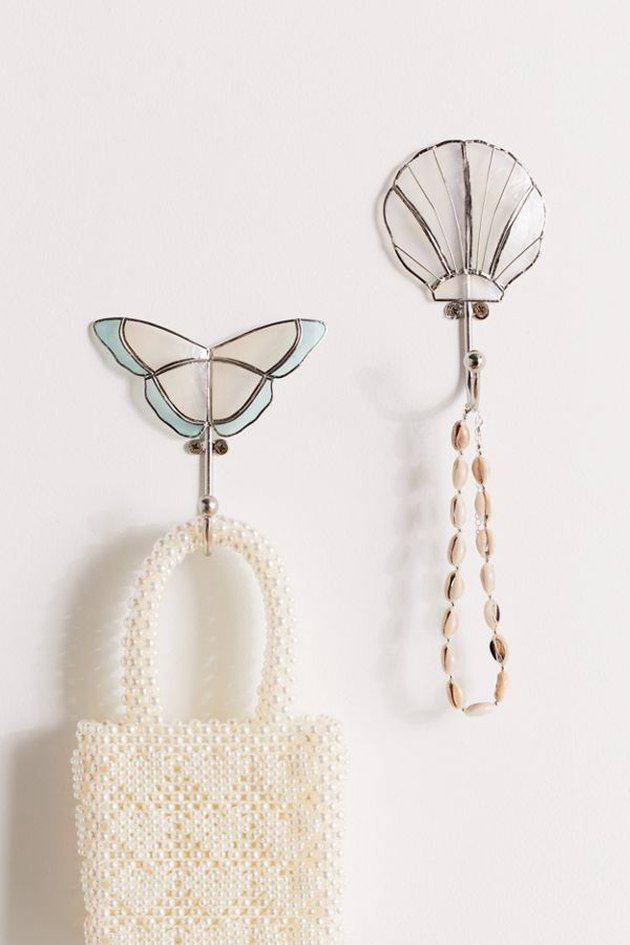 two wall hooks in the shape of a butterfly and a shell