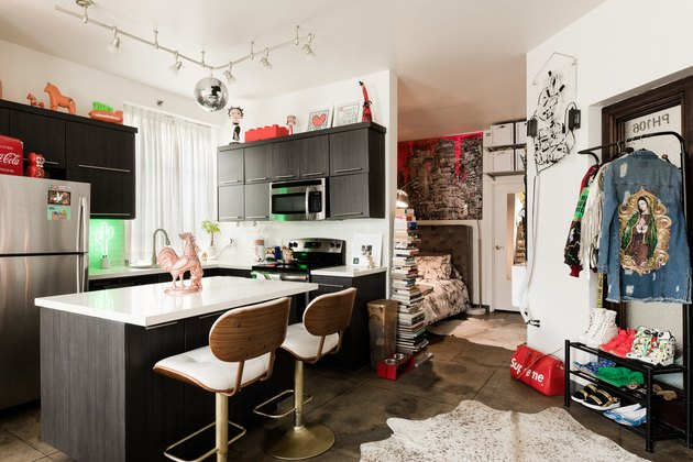 kitchen with concrete floor, stainless steel appliances, island, red accents