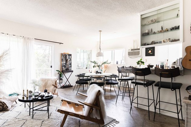 open living space with concrete floors, kitchen, dining table, sheer curtains