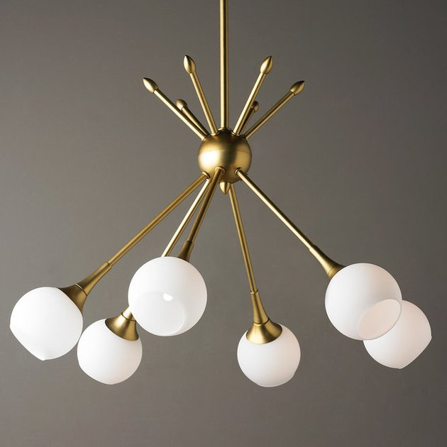 Mod chandelier with six brass arms meeting in the middle in a tent shape and white globes at the end of each arm