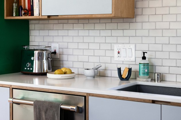 close up on white kitchen countertop with upper and lower cabinets and subway tile backsplash