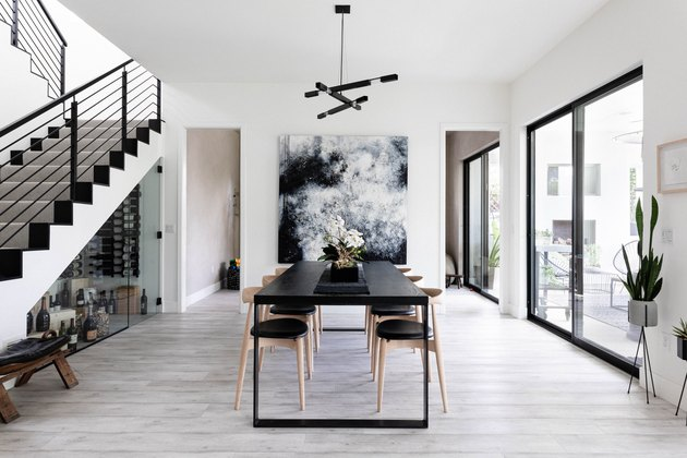 dining room with exposed stairs black table, large graphic artwork, hardwood floors