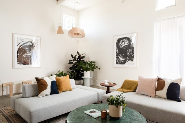living room with modern sofas, pendant lights, taupe walls, concrete floors