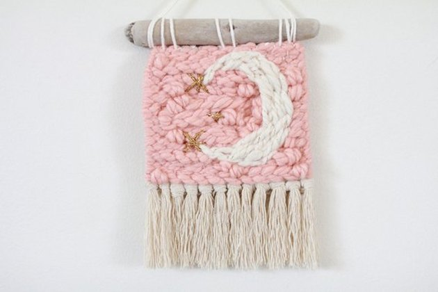 Small light pink woven art with beige fringe and white crescent moon