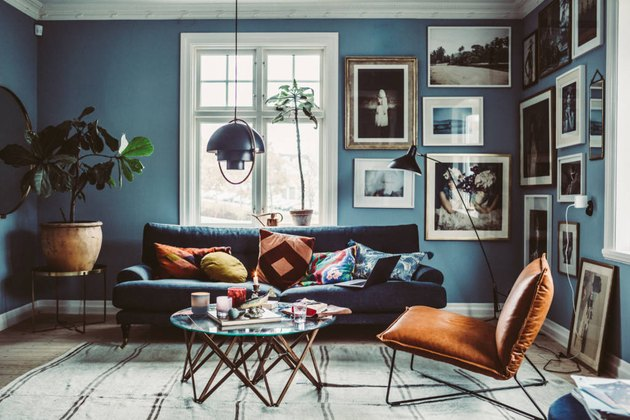 Blue living room with eclectic gallery wall and leather lounge chair