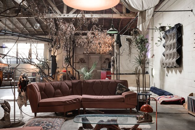 large space with plants, sectional couch, concrete floors