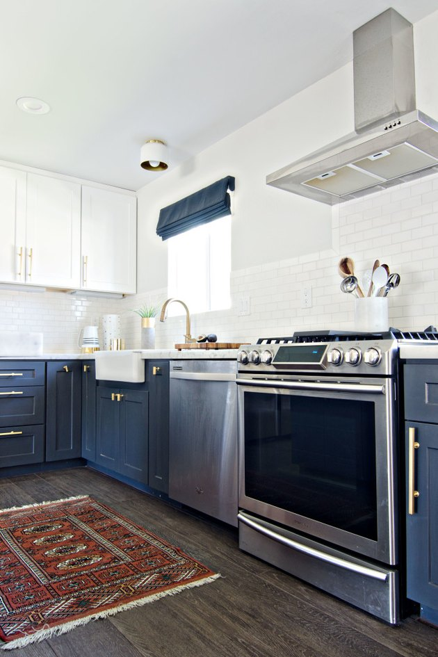 White and navy blue kitchen color idea with vintage rug and midcentury light fixture