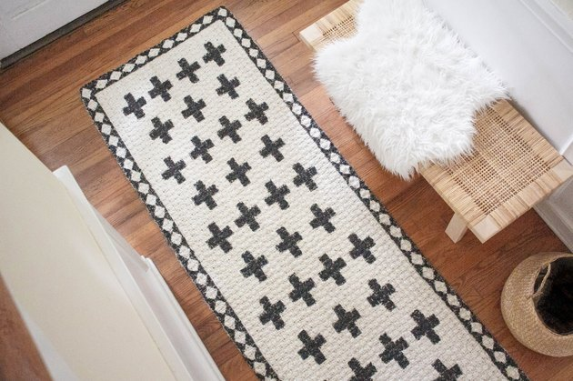 Natural jute rug painted with black patterns and design next to bench with sheepskin rug