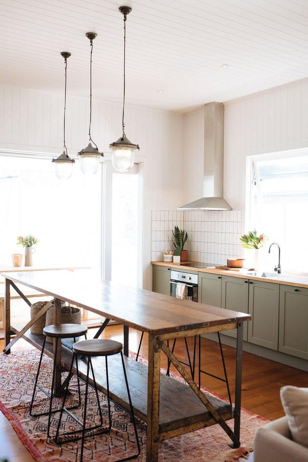 olive green kitchen color idea with wood countertops and pendant lights