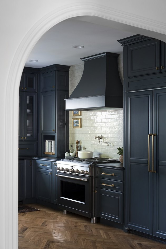 Dark navy blue kitchen color idea with white subway tile backsplash and brass hardware