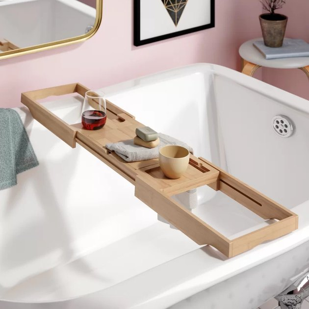 Extendable bamboo bathtub caddy holding glass of wine and wash cloth