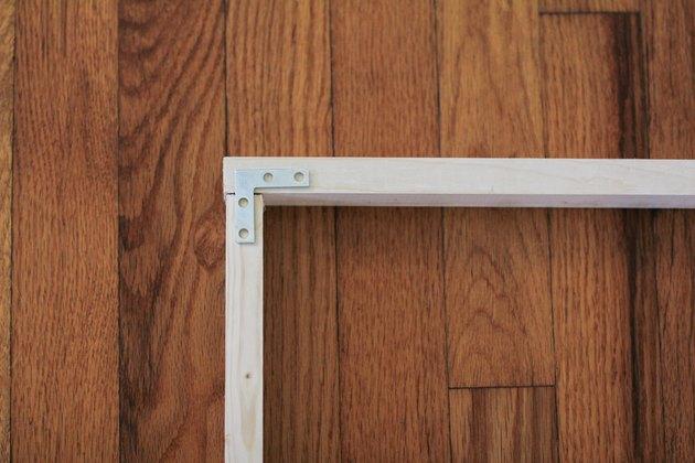 Corner of wood frame fastened with flat corner brace