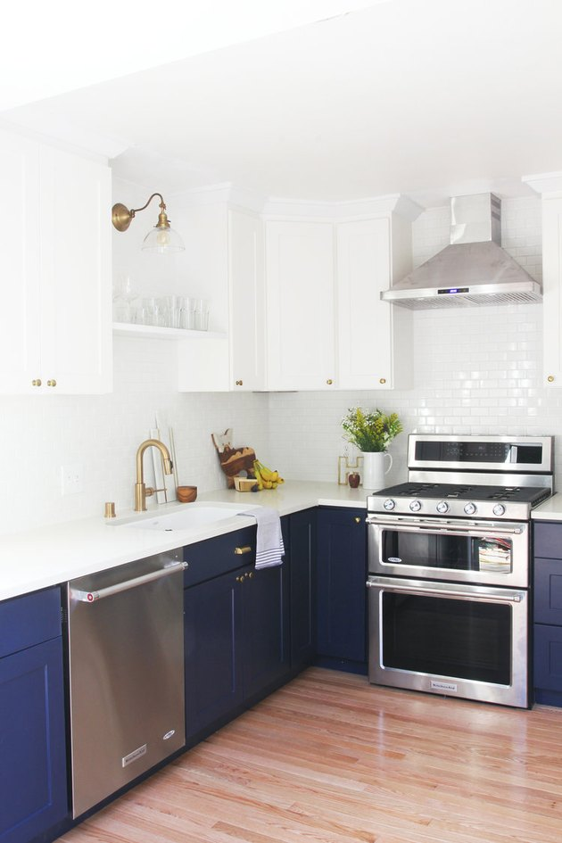 White and navy blue kitchen color idea with silver appliances and white tile backsplash