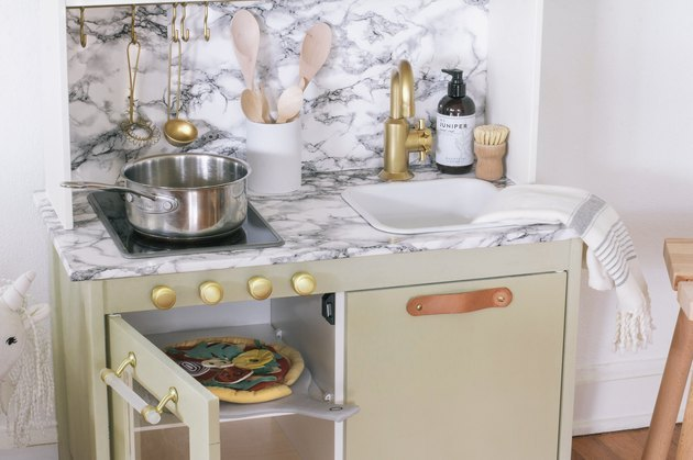 Add modern glam to the IKEA Duktig play kitchen with marble and brass accents.