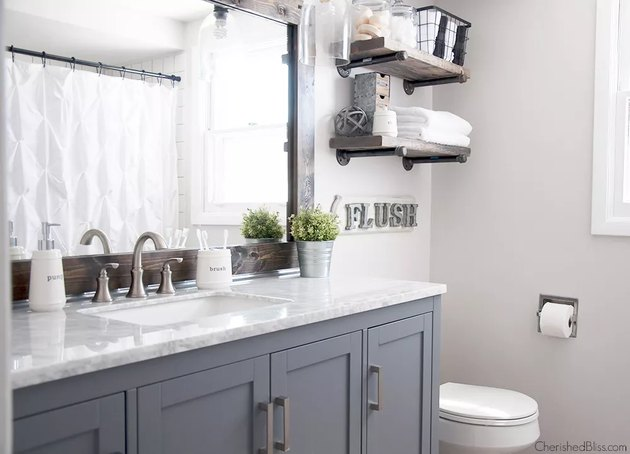 small farmhouse bathroom idea with gray cabinets and rustic mirror