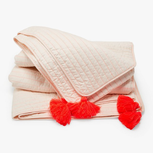 coral embroidered quilt with pom pom fringe