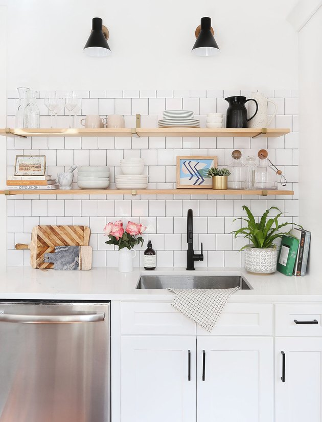 white kitchen with single bowl stainless steel sink and open shelving