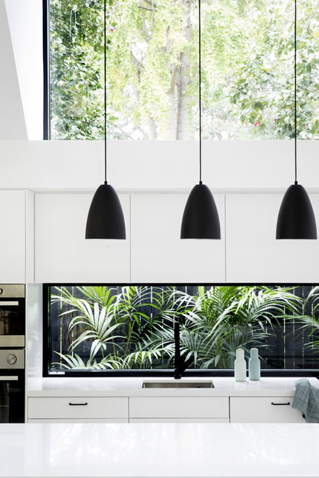 all-white modern kitchen with black pendant lights and single-bowl sink