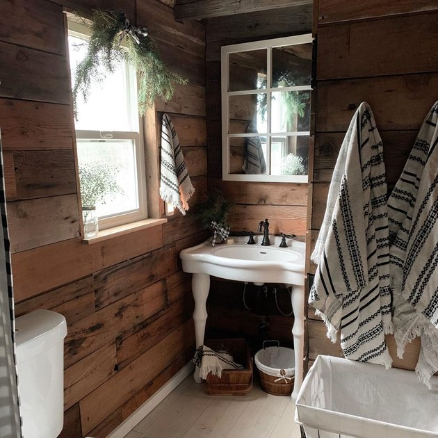 small farmhouse bathroom idea with wood shiplap walls and pedestal sink