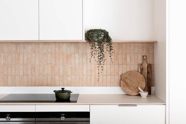 white kitchen with exposed vertical terra cotta brick backsplash