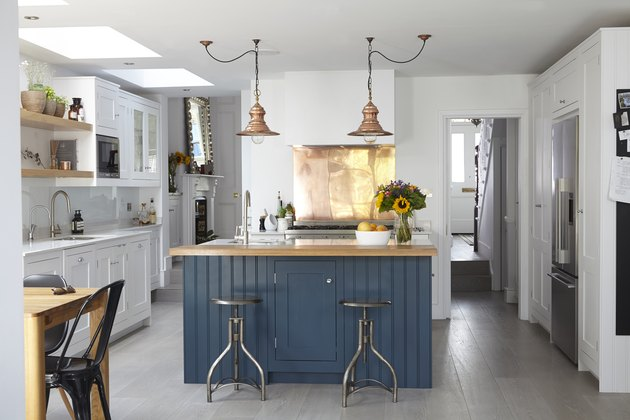 white kitchen with blue island and copper lighting above with copper backsplash