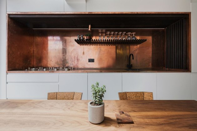 white and walnut kitchen with entire copper backsplash