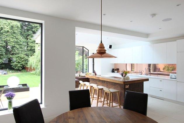 white kitchen with copper backsplash and large island