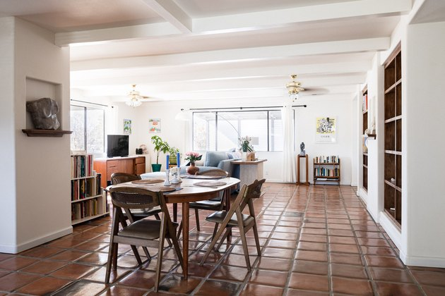 dining and living areas with clay tile floor