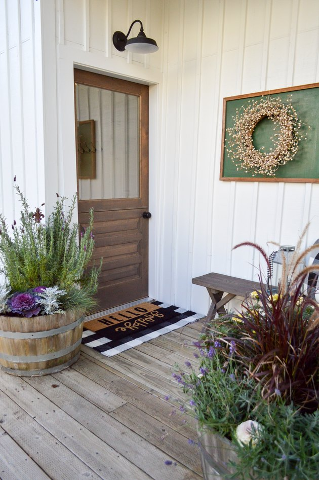 Farmhouse front door idea with flea market decor and potted plants