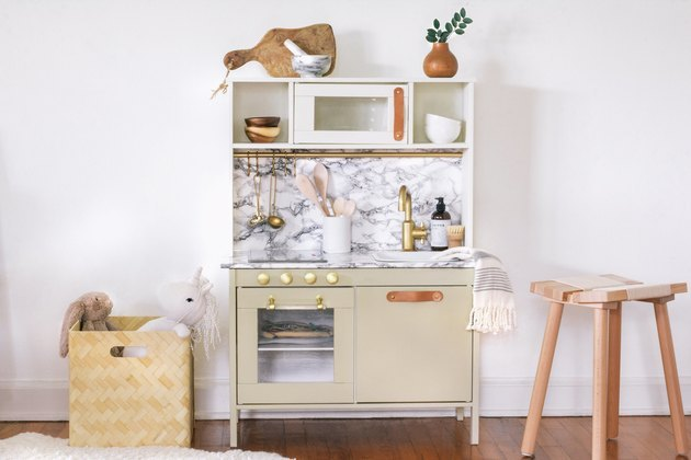 IKEA play kitchen with added marble paper and brass and leather handles.