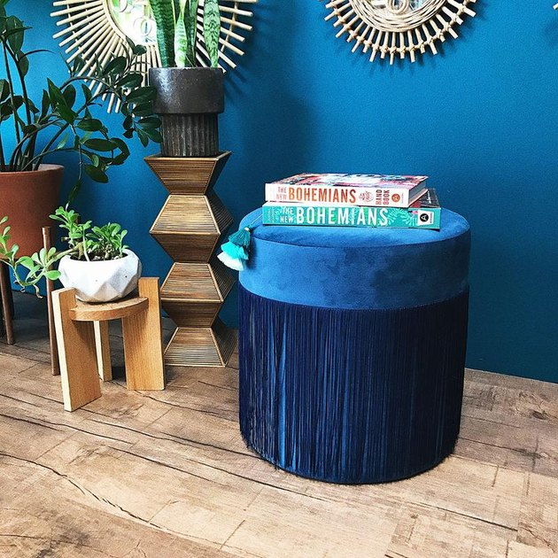 room with blue wall and blue velvet pouf
