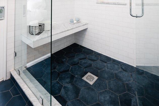 blue hexagon shower floor tile, silver square drain, built-in shower bench, glass shower door, white subway tile wall