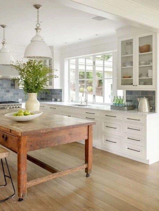 white kitchen with rustic kitchen island  and blue subway tile backsplash