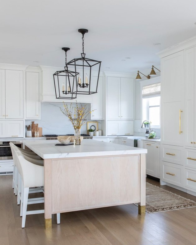 white kitchen with light wood island and brass hardware
