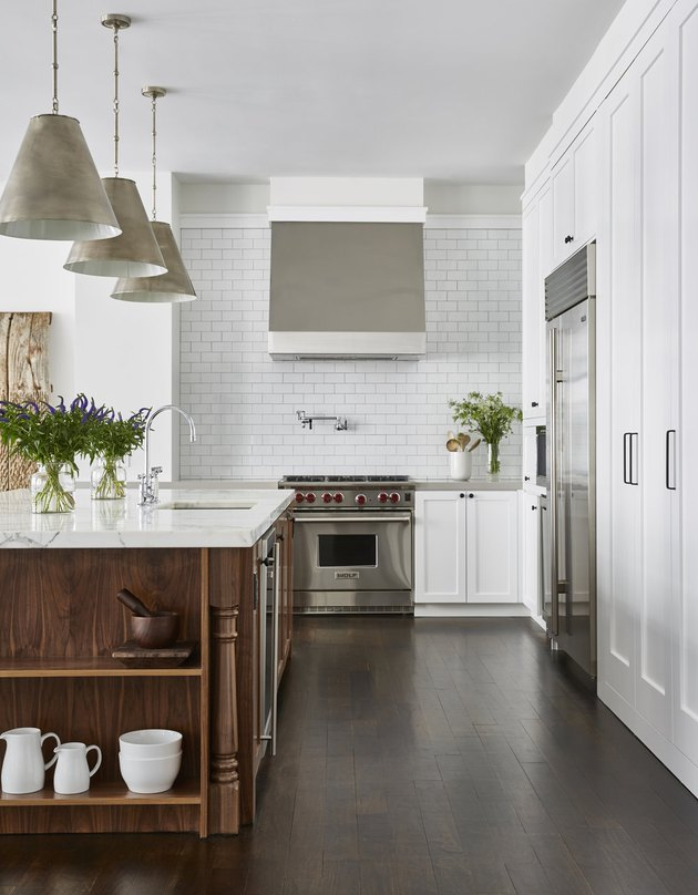 white kitchen with espresso wood island and subway tile