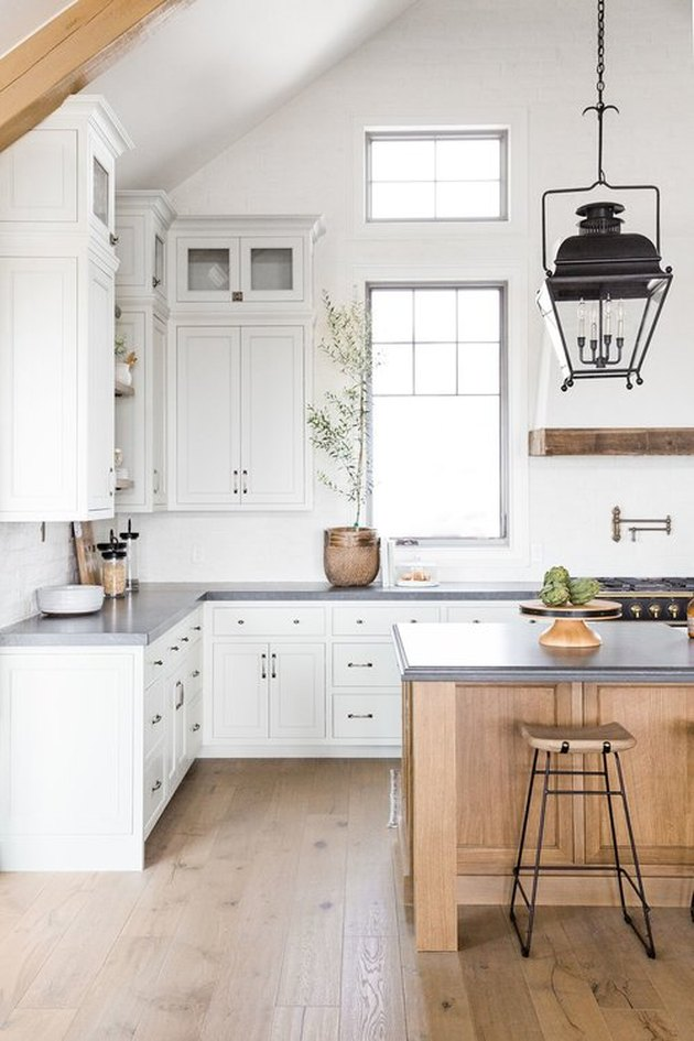 white kitchen with grey countertops and wood island