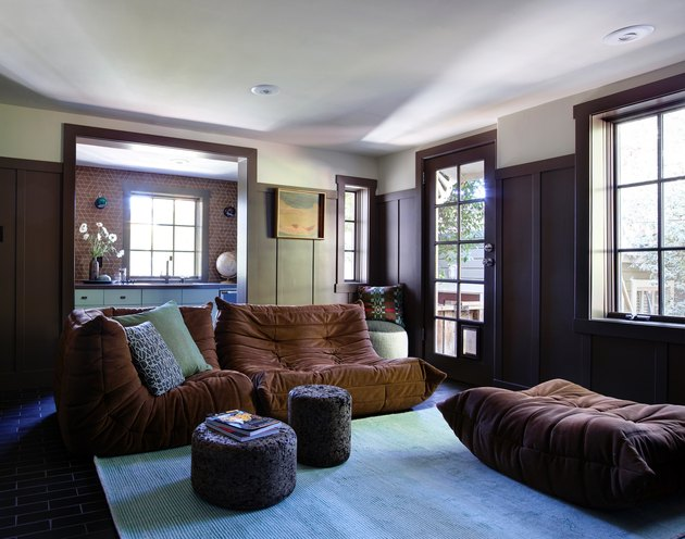 Family room with brown furniture, wood paneling, and turquoise carpet