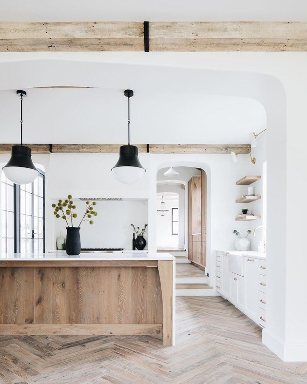 white wood and black kitchen with rustic wood island and herringbone floors