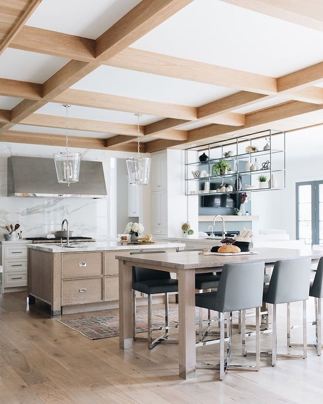 modern white kitchen with grey wood island and wood ceiling detail