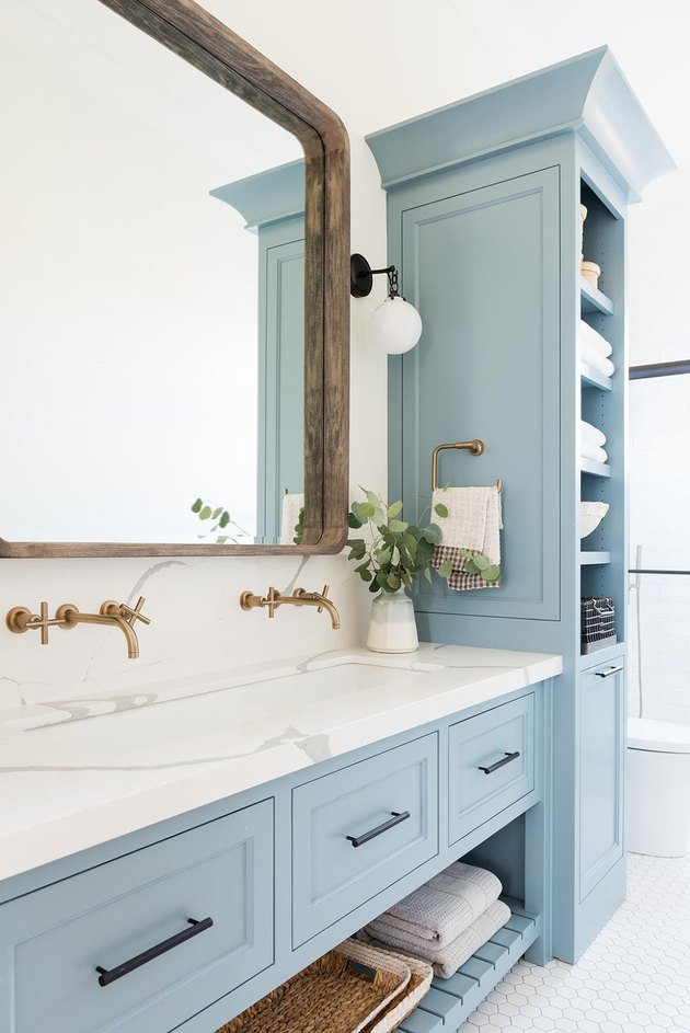 Sky blue bathroom cabinets with white countertop and large mirror