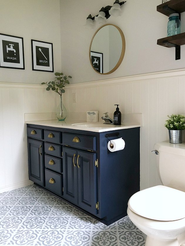 Navy blue bathroom cabinets with cement tile floor and wainscoting