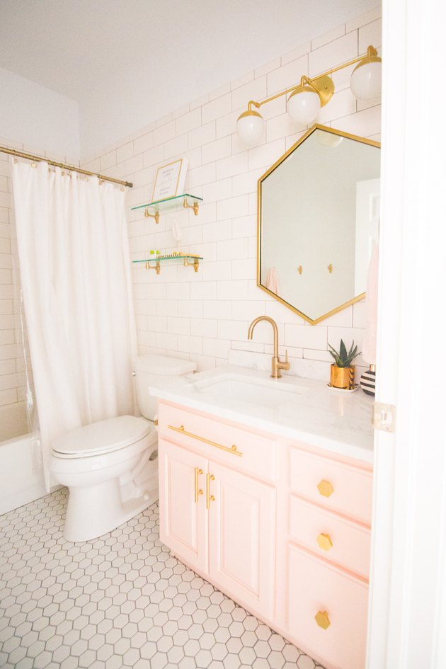 Blush bathroom cabinets with geometric mirror and gold hardware