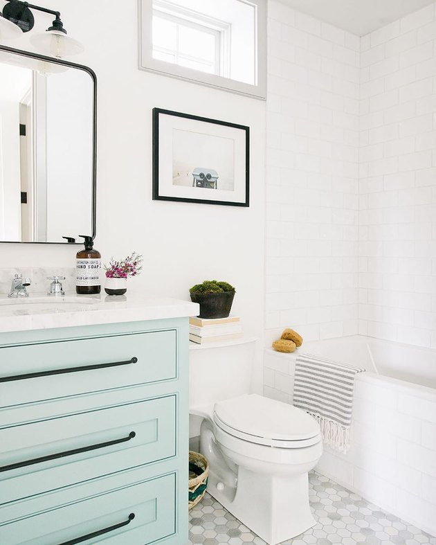 Mint bathroom cabinets in white bathroom with black hardware